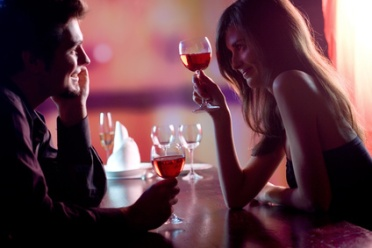 Young couple sharing a glass of red wine in restaurant